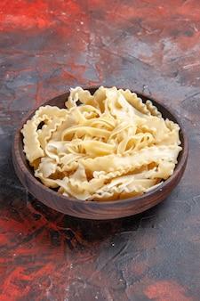 Vorderansicht geschnittener roher teig innerhalb platte auf dunkler oberfläche teignudeln rohes dunkles essen