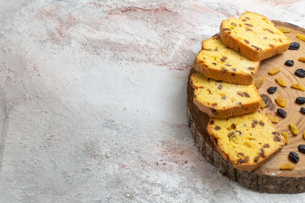 Vorderansicht geschnittener rosinenkuchen mit frischen rosinen auf dem hellweißen schreibtisch
