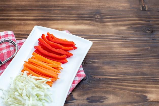 Vorderansicht geschnittenes gemüse karottenpaprika und kohl auf brauner oberfläche