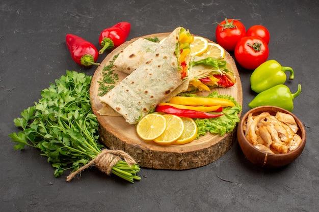 Vorderansicht geschnittenes shaurma-fleischsandwich mit zitronenscheiben und grüns auf dunklem raum