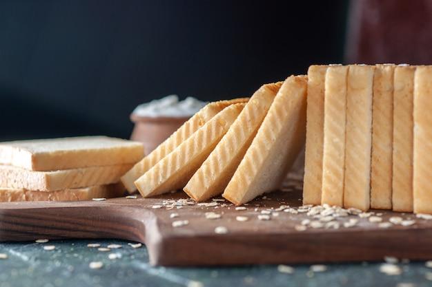 Vorderansicht geschnittenes weißbrot auf dunklem hintergrund tee frühstück essen morgen brotbäckerei teig brötchen gebäck