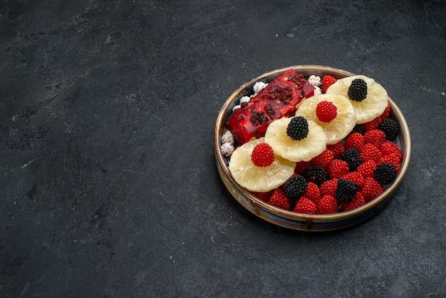 Vorderansicht getrocknete ananasringe mit confiture beeren auf dunkelgrauen oberflächenfrüchten trockene rosinen süße zuckersüßigkeiten