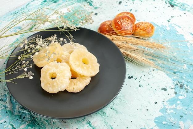 Vorderansicht getrocknete ananasringe mit kleinen keksen auf blauer oberfläche