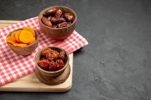 Vorderansicht getrocknete aprikosen mit khurma auf grauer oberfläche trägt trockene rosinen früchte
