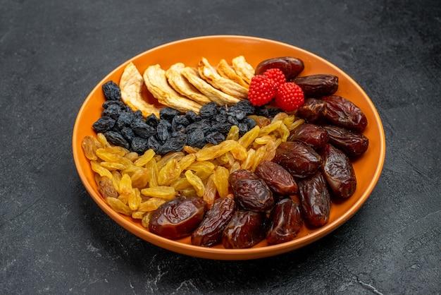 Vorderansicht getrocknete früchte mit rosinen innerhalb platte auf dem grauen raum