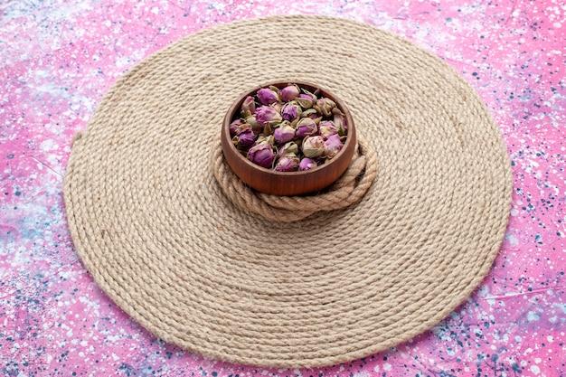Vorderansicht getrocknete kleine blumen mit seilen auf rosa schreibtisch. blumenfarbfotohintergrund.