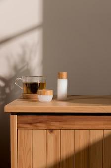 Vorderansicht glas tee neben kosmetischen produkten
