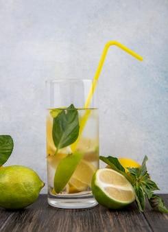 Vorderansicht glas wasser mit gelber strohminze zitrone und limettenschnitzen
