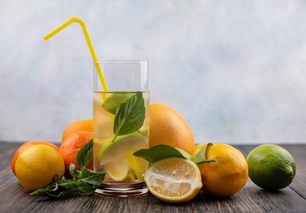 Vorderansicht glas wasser mit scheiben zitronenlimette und minze mit gelbem stroh und grapefruit mit orangen auf holzhintergrund