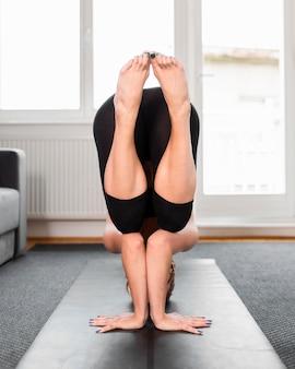 Vorderansicht gleichgewicht praktizierendes yoga zu hause konzept