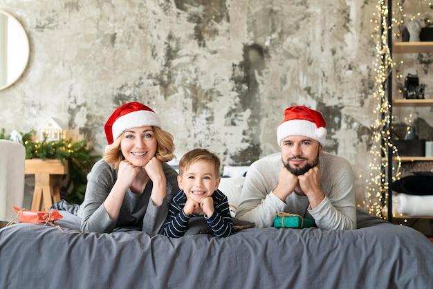 Vorderansicht glücklicher junge und eltern, die am weihnachtstag zusammen sind