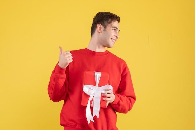Vorderansicht glücklicher junger mann, der auf gelb steht