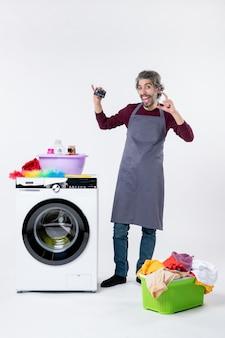 Vorderansicht glücklicher junger mann, der die karte in der nähe des wäschekorbs der waschmaschine auf weißem hintergrund hält