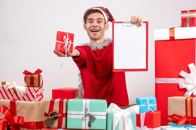 Vorderansicht glücklicher junger mann, der um weihnachtsgeschenke sitzt