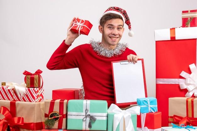 Vorderansicht glücklicher junger mann, der zwischenablage hält, die um weihnachtsgeschenke sitzt