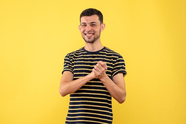 Vorderansicht glücklicher junger mann im schwarzen und weißen gestreiften t-shirt gelben isolierten hintergrund