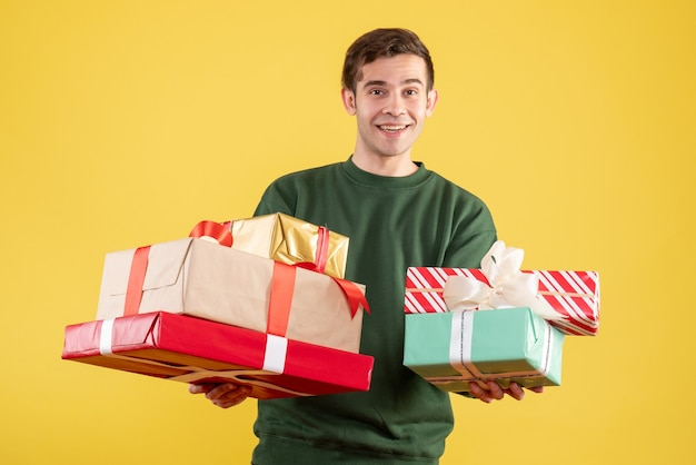 Vorderansicht glücklicher junger mann mit grünem pullover, der auf gelb steht