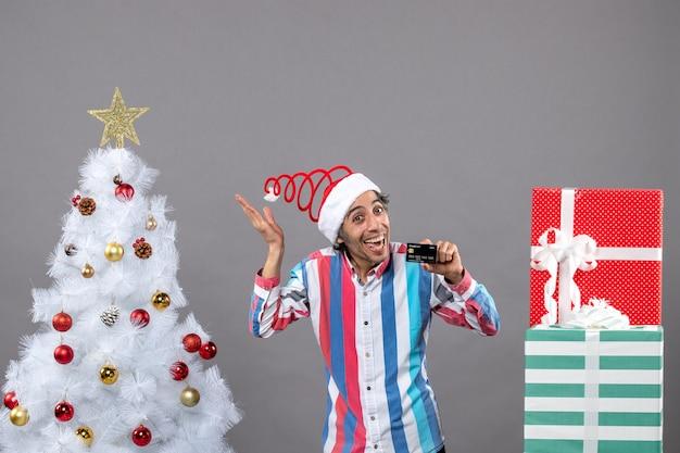 Vorderansicht glücklicher junger mann mit kreditkarte, die weihnachtsstern zeigt