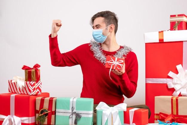 Vorderansicht glücklicher junger mann mit maske, die stärke zeigt, die um weihnachtsgeschenke sitzt