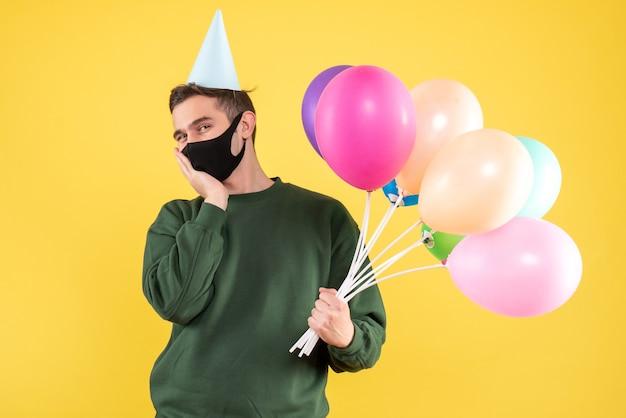 Vorderansicht glücklicher junger mann mit partykappe und bunten luftballons, die auf gelb stehen