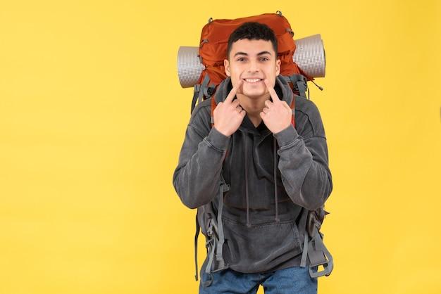 Vorderansicht glücklicher junger mann mit rotem rucksack, der auf sein lächeln zeigt
