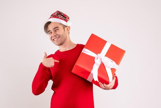 Vorderansicht glücklicher junger mann mit weihnachtsmütze, die auf sich auf weiß zeigt