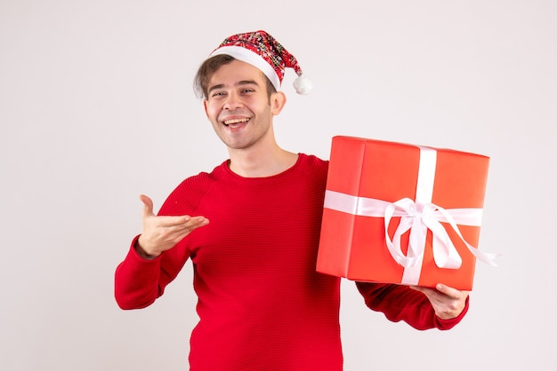 Vorderansicht glücklicher junger mann mit weihnachtsmütze, die auf weiß steht