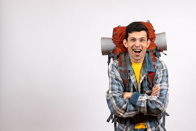 Vorderansicht glücklicher junger reisender mit rucksack, der hände kreuzt