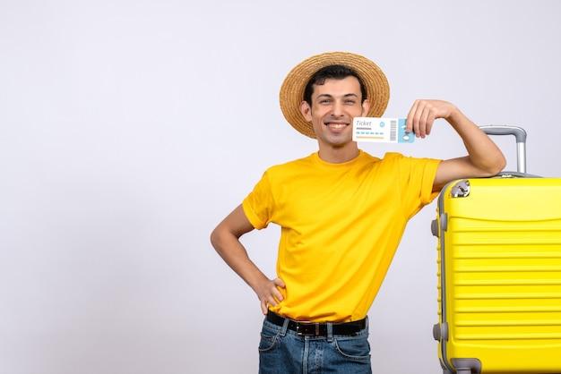 Vorderansicht glücklicher junger tourist, der nahe gelbem koffer steht, der hand auf eine taille hält, die flugschein hält