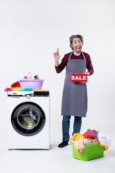 Vorderansicht glücklicher kerl in schürze, der das verkaufsschild hochhält, das in der nähe der waschmaschine auf weißem hintergrund steht