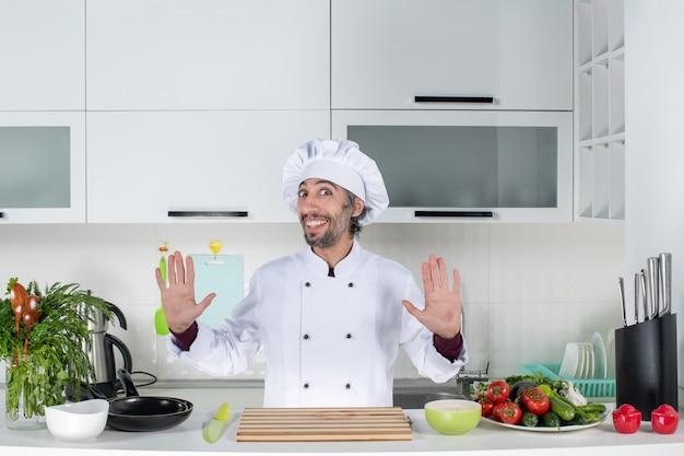 Vorderansicht glücklicher männlicher koch in uniform, der hinter küchentisch in der modernen küche steht