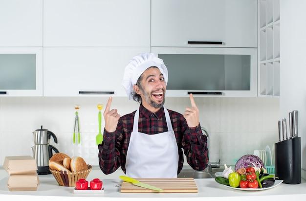 Vorderansicht glücklicher mann, der hinter küchentisch in der küche steht