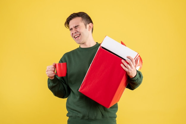 Vorderansicht glücklicher mann mit grünem pullover, der großes geschenk und rote tasse steht auf gelb hält