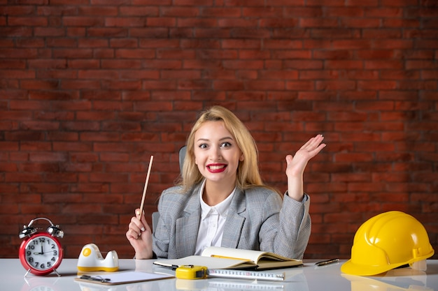Vorderansicht glücklicher weiblicher ingenieur, der hinter ihrem arbeitsplatz sitzt