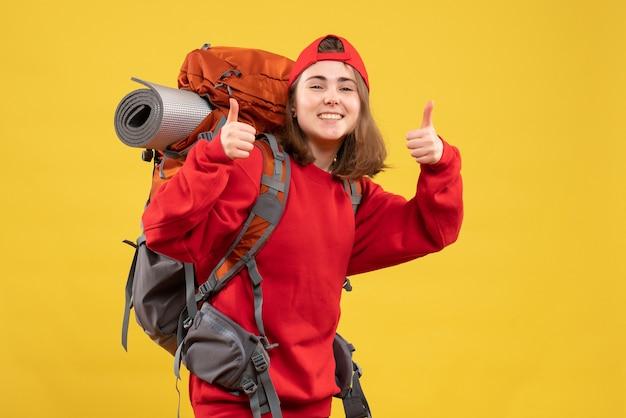 Vorderansicht glücklicher weiblicher reisender mit rucksack, der daumen aufgibt