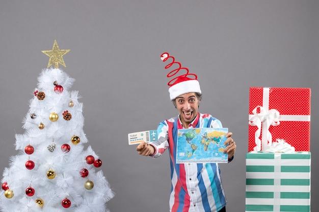 Vorderansicht glücklicher weihnachtsmann, der weltkarte und reiseticket hält