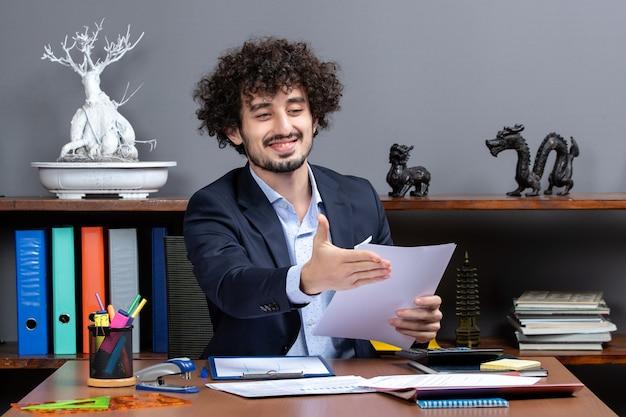 Vorderansicht glückseliger geschäftsmann, der am schreibtisch sitzt und ein neues projekt bespricht