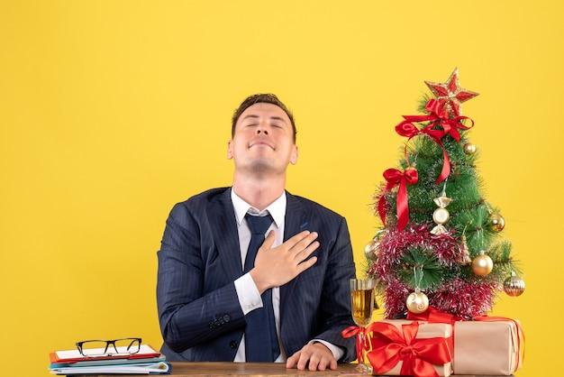 Vorderansicht glückseliger mann, der hand auf seine brust setzt, die am tisch nahe weihnachtsbaum sitzt und auf gelbem hintergrund präsentiert