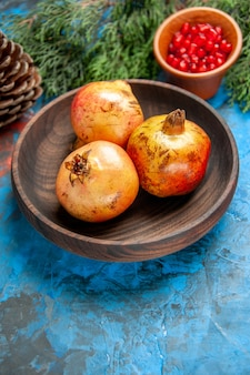 Vorderansicht granatäpfel auf holzplatte granatapfelkerne in holzschale kiefernzweig und kegel auf blau