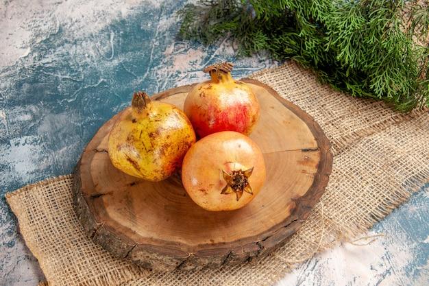 Vorderansicht granatäpfel auf rundem baumholz schneidebrett kiefernzweig auf blau-weißem hintergrund