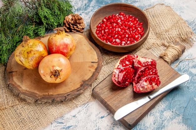 Vorderansicht granatäpfel auf rundem schneidebrett granatapfelkerne in schüssel ein geschnittener granatapfel