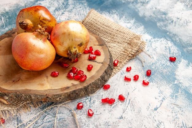Vorderansicht granatäpfel auf rundem schneidebrett verstreute granatapfelkerne auf blau-weiß