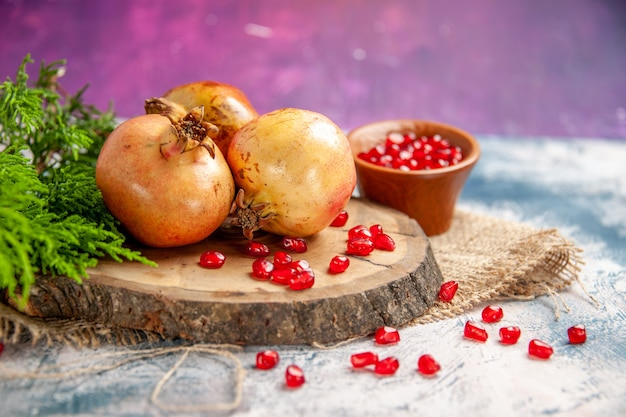 Vorderansicht granatäpfel auf rundem schneidebrett verstreute granatapfelkerne in schüssel auf rosa freiem platz