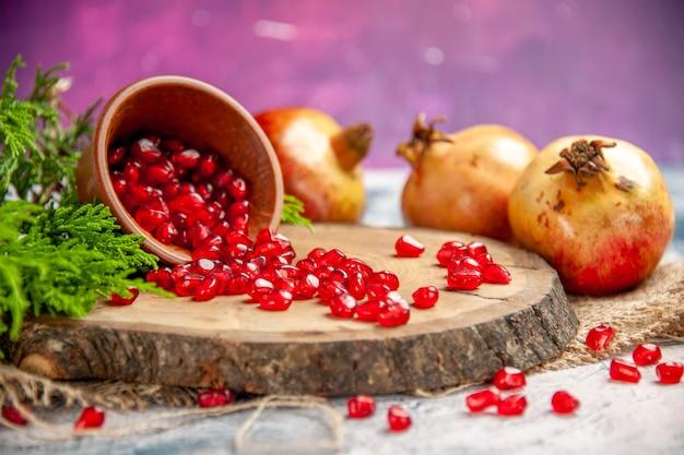Vorderansicht granatäpfel verstreut granatapfelkerne in schüssel auf baumholzbrett auf rosa
