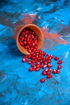 Vorderansicht granatapfelkerne in kleiner holzschale auf blauem hintergrund mit freiem platz