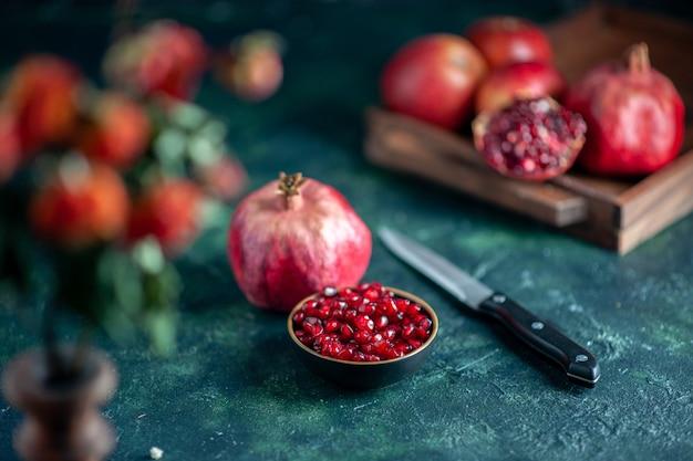 Vorderansicht granatapfelkerne schüssel messer granatäpfel auf holzbrett auf dunkler oberfläche
