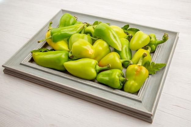 Vorderansicht grüne paprika im rahmen auf weißem pfeffer farbe reife mehlpflanze foto gemüsesalat