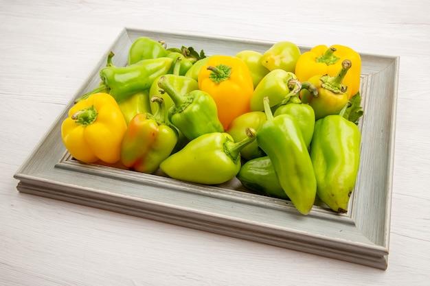 Vorderansicht grüne paprika im rahmen auf weißem pfefferfarbe reifes pflanzengemüsesalatfoto