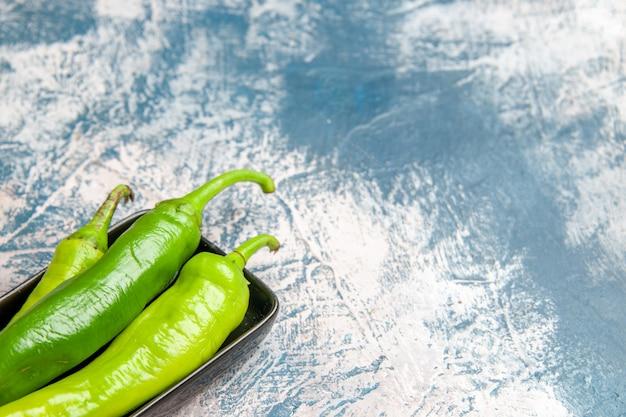 Vorderansicht grüne peperoni auf schwarzem teller auf blau-weißem hintergrund freiraum
