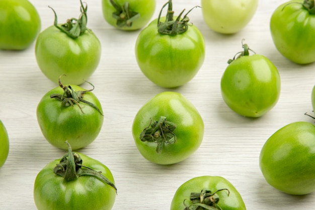 Vorderansicht grüne tomaten auf weißem schreibtisch farbe reife salatfotomahlzeit gesunde lebensdiät